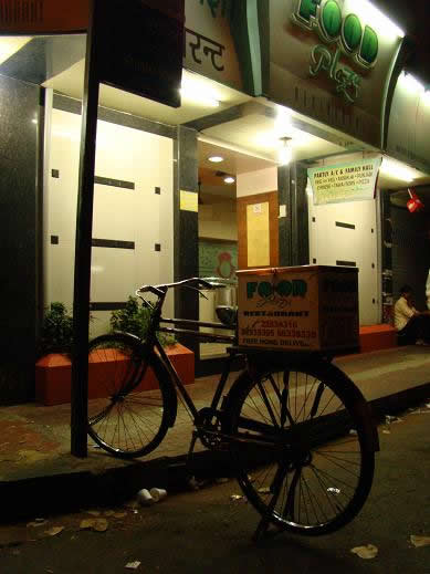 A delivery bicycle belonging to Food Plaza, take away pizzas