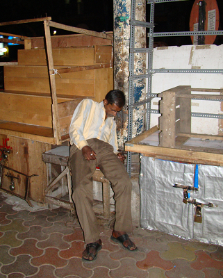 With his stock locked away, this street trader takes no chances and sleeps on a stool next to his wares.