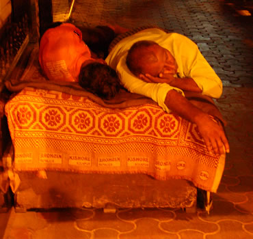 The habit is not confined to the young, some shopkeepers prefer it. In 30 degrees heat, Bombay is easy to sleep at night. This man and wife sleep on a bed they drag out of a store backroom each night to also keep gurad of their shop front.